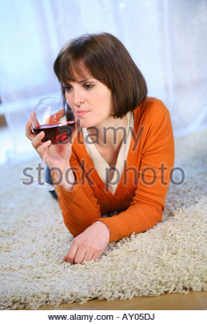 young woman lying on a carpet and drinking red wine - Stock Photo