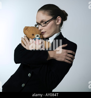studio shot portrait of a beautiful young woman in a costume suit holding a teddy bear - Stock Photo
