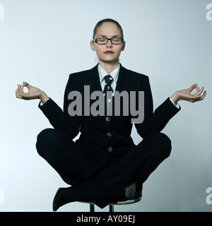 studio shot portrait of a beautiful young woman in a costume suit sitting on the lotus posture - Stock Photo