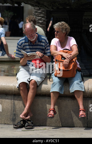 Tourists Reading Guide Book Placa Reial Barcelona Spain - Stock Photo