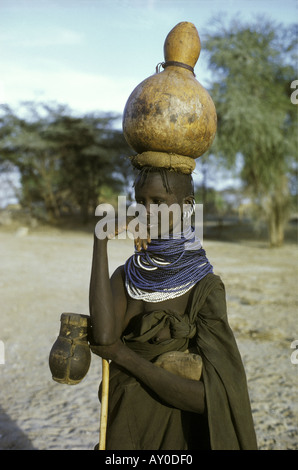 Turkana married woman carrying a gourd of water on her head Lokichar northern Kenya East Africa - Stock Photo