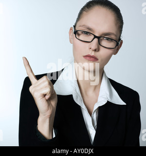 studio shot portrait of a beautiful young and strict woman in a costume suit - Stock Photo