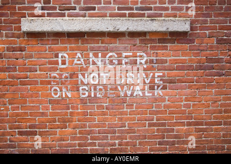 Sign stenciled on a brick wall 'Do Not Drive on Sidewalk' - Stock Photo