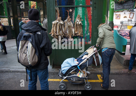 A man transfixed by hares for sale next to a woman and baby in London's Borough market - Stock Photo