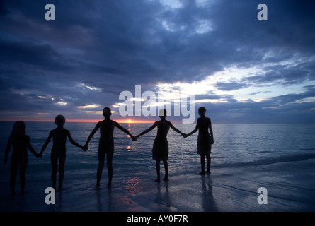 Children with outstretched arms holding hands at sunset silhouette - Stock Photo