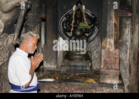 Male worshiper praying in front of a Ganesh shrine, Meenakshi Temple, Madurai, Tamil Nadu, India - Stock Photo