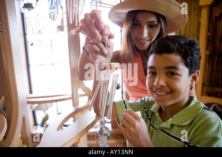 Young woman with her son holding a wind chime in store - Stock Photo