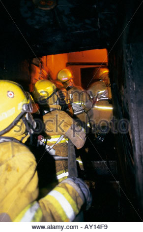 Firefighters advance a hose line inside a house during a live-fire training drill. - Stock Photo