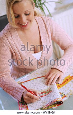 woman solves crossword - Stock Photo