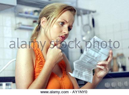 woman taking medicine reading instruction leaflet - Stock Photo