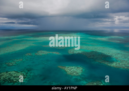Towering cumulonimbus cloud over an aerial view of the Great Barrier Reef of Australia - Stock Photo