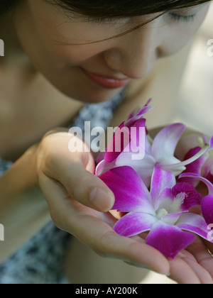 Close-up of a young woman smelling orchids - Stock Photo