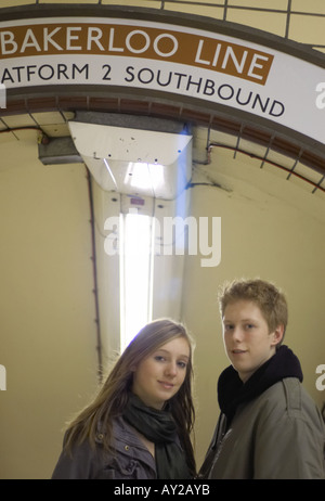 a teenage couple aged 16 on day trip to London tired at end of day descending to Tube Station - Stock Photo