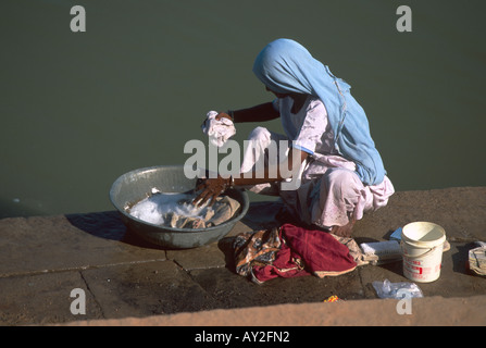 Lone woman washing clothing in a tank, Sarkhej outside of Ahmedabad in the state of Gujarat, India. - Stock Photo