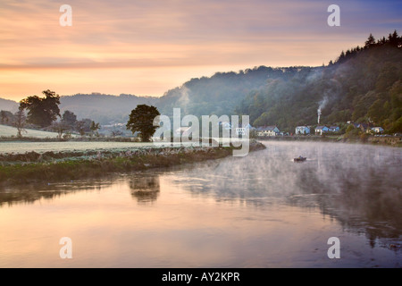 Smoke rises from a cottage chimney on a cold misty dawn on the river Wye at the village of Tintern, South Wales - Stock Photo