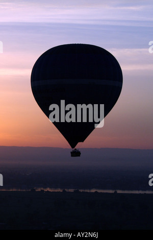 Hot Air Balloon Silhouetted in Front of Beautiful Sunset over the River Nile [Near Luxor, Egypt, Arab States, Africa]. - Stock Photo