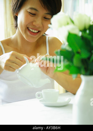Young woman pouring tea into a cup and smiling - Stock Photo