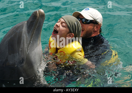 Dolphin therapy Lucas Knecht who is mentally and fysically disabled in the water with therapist Marcus of Dolphin - Stock Photo
