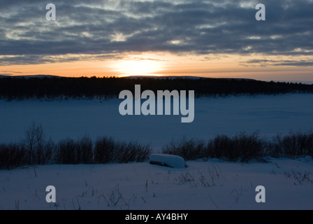 A river boat buried in snow at the shore of tornio river in finnish lapland - Stock Photo