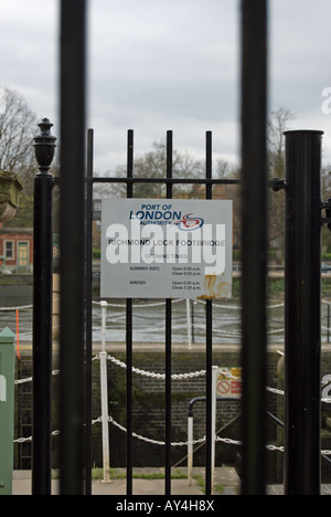 seen through railings, a sign gives opening times for richmond lock footbridge, on the river thames in richmond, - Stock Photo