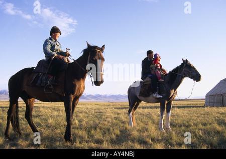 Horse riding boys, Lake Song Kul, Kirgizia - Stock Photo