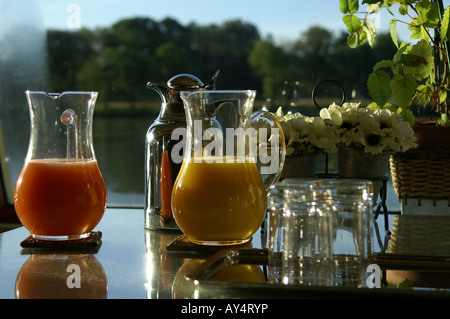 Sparkling glass pitchers of juice on a table beside the Rhone - Stock Photo