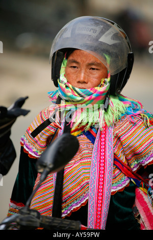Flower Hmong woman wearing motorcycle crash helmet - Stock Photo