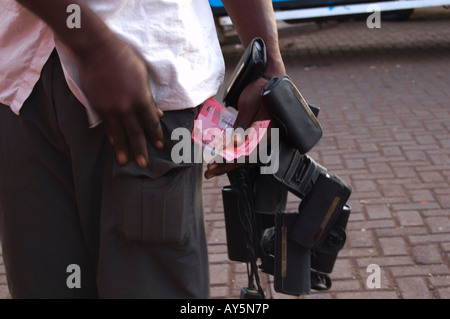 A Street Seller Tending Change with the New Ghana Cedi at Tamale Bus Station, Ghana - Stock Photo