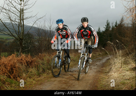 Two cross country mountain bikers ride along a muddy track - Stock Photo