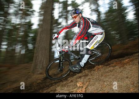 A mountain biker rides his bike along a dirt track - Stock Photo