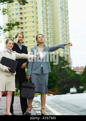 Two business women hailing a taxi while the other one talking on the phone - Stock Photo