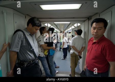 The subway riders in the subway rail car, two lovers passengers are kissing. - Stock Photo