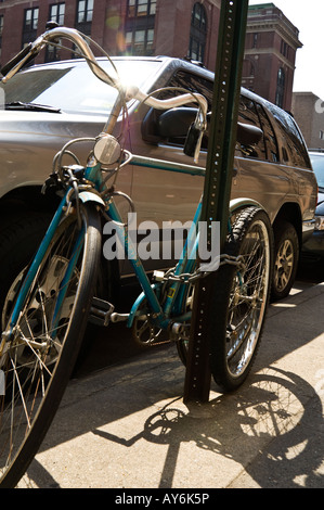 Bicycle chained to signpost beside parked SUV - Stock Photo