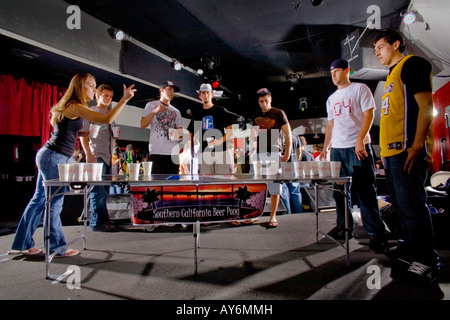 Players watch a woman tosses a ping pong ball during a beer pong competition in Los Angeles Beer pong also called - Stock Photo