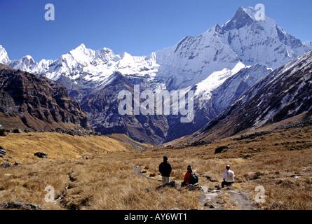 Trekkers admiring the view of Machhapuchhare from Annapurna Base Camp in the Annapurna Sanctuary Nepal - Stock Photo