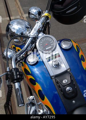Blue fuel tank of a customized Harley Davidson motorcycle with speedometer and helmet hanging from the handlebars - Stock Photo