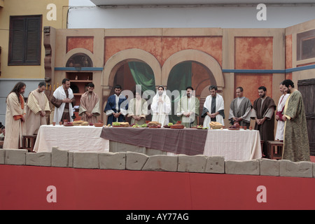 actors playing jesus and his 12 disciples sit down to enact the last supper in the