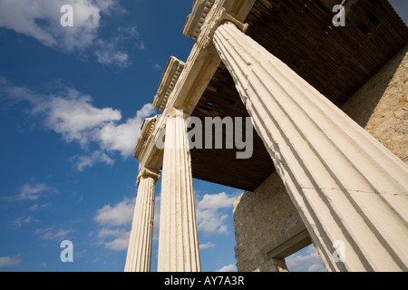 Soaring Columns and Sky Three columns of the partially rebuilt stoa in front of a ruined temple in this Ionian Greek - Stock Photo