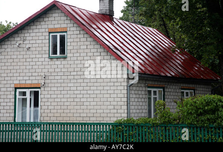 Two story house with bright red metal roof. Green trim on bottom of house. Tree in background - Stock Photo
