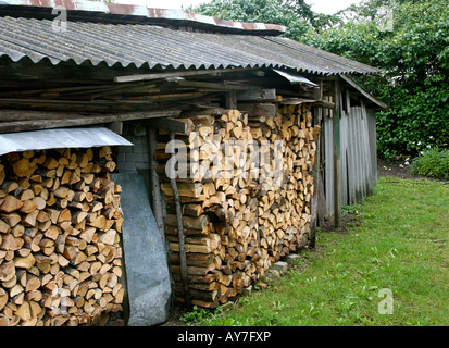 Outdoor woodshed with open front and sheet metal roof. Grass in front and shrubs in background. - Stock Photo