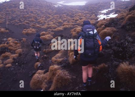 Couple Tramping on the Tongariro Crossing Tongariro National Park North Island New Zealand - Stock Photo