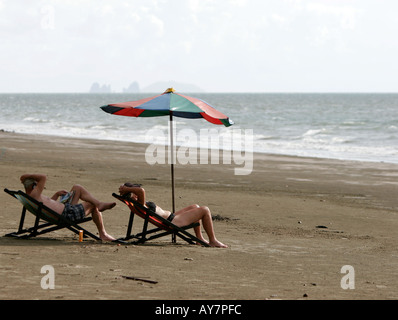 Couple relax in deckchairs under umbrella Lo Yai beach Ko Sukorn island Thailand - Stock Photo