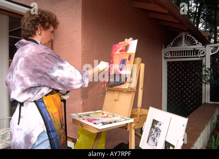 A local artist demonstrates her painting technique, at the Street Players Festival in downtown Ruidoso, New Mexico. - Stock Photo