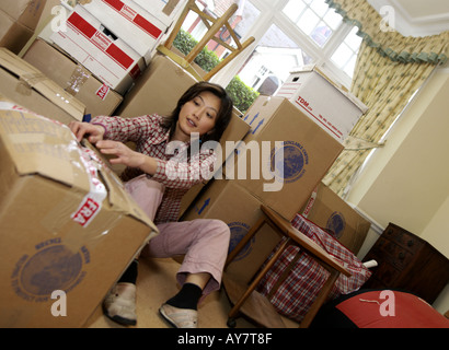 a young woman relaxes happy after move into new home - Stock Photo