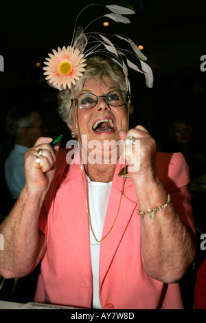 Older woman in Melbourne Cup outfit and hat cheers watching her winning horse on television Australia - Stock Photo