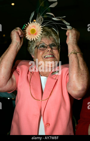 Older woman in Melbourne Cup outfit jumps up cheering her winning horse on television Australia - Stock Photo