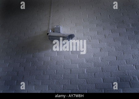 CCTV video camera on white brick wall surveillance - Stock Photo