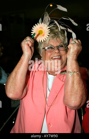 Older woman in Melbourne Cup outfit jumps up cheering her winning Cup horse on television Australia - Stock Photo