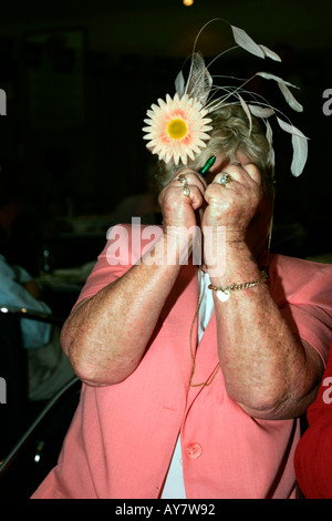 Older woman in Cup outfit celebrates as afer backing the winning horse in the Melbourne Cup Australia - Stock Photo