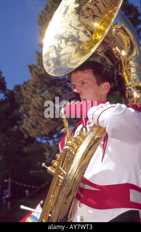A high school teenager marching band member, plays his brass tuba at the Aspenfest Parade in downtown Ruidoso, New - Stock Photo